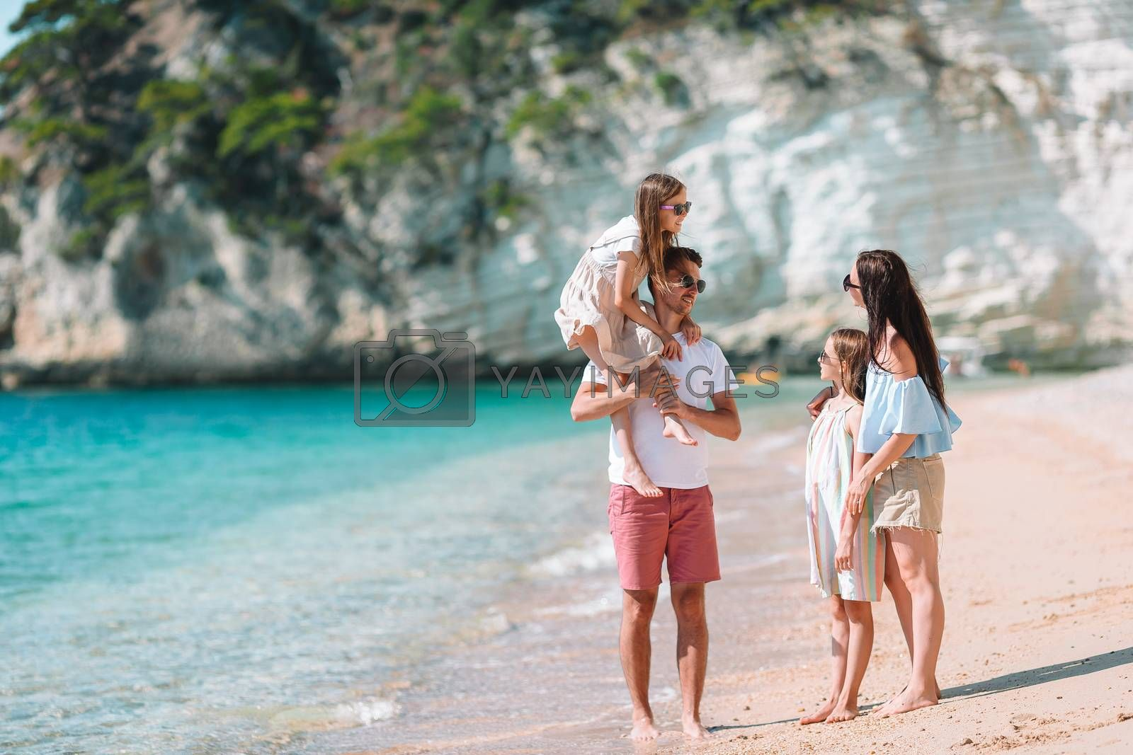 Happy family on the beach. People having fun on summer vacation. Father, mother and children against blue sea and mountains background. Holiday travel concept