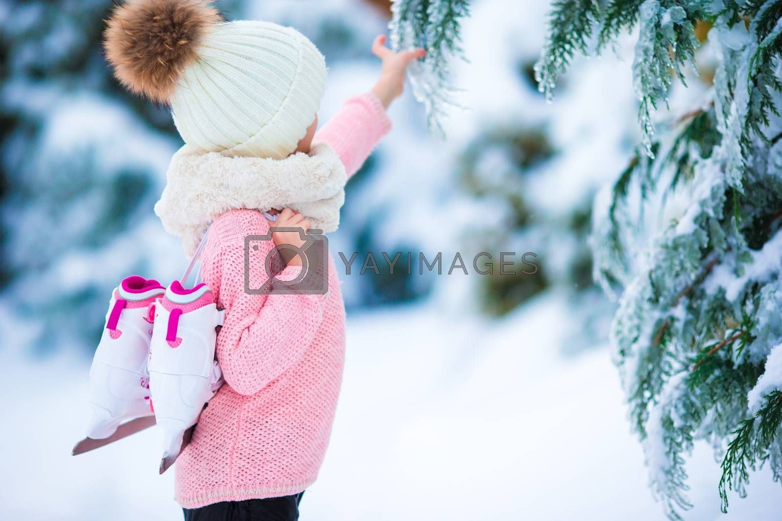 Adorable little girl going to skate in warm winter snow day outdoors by travnikovstudio