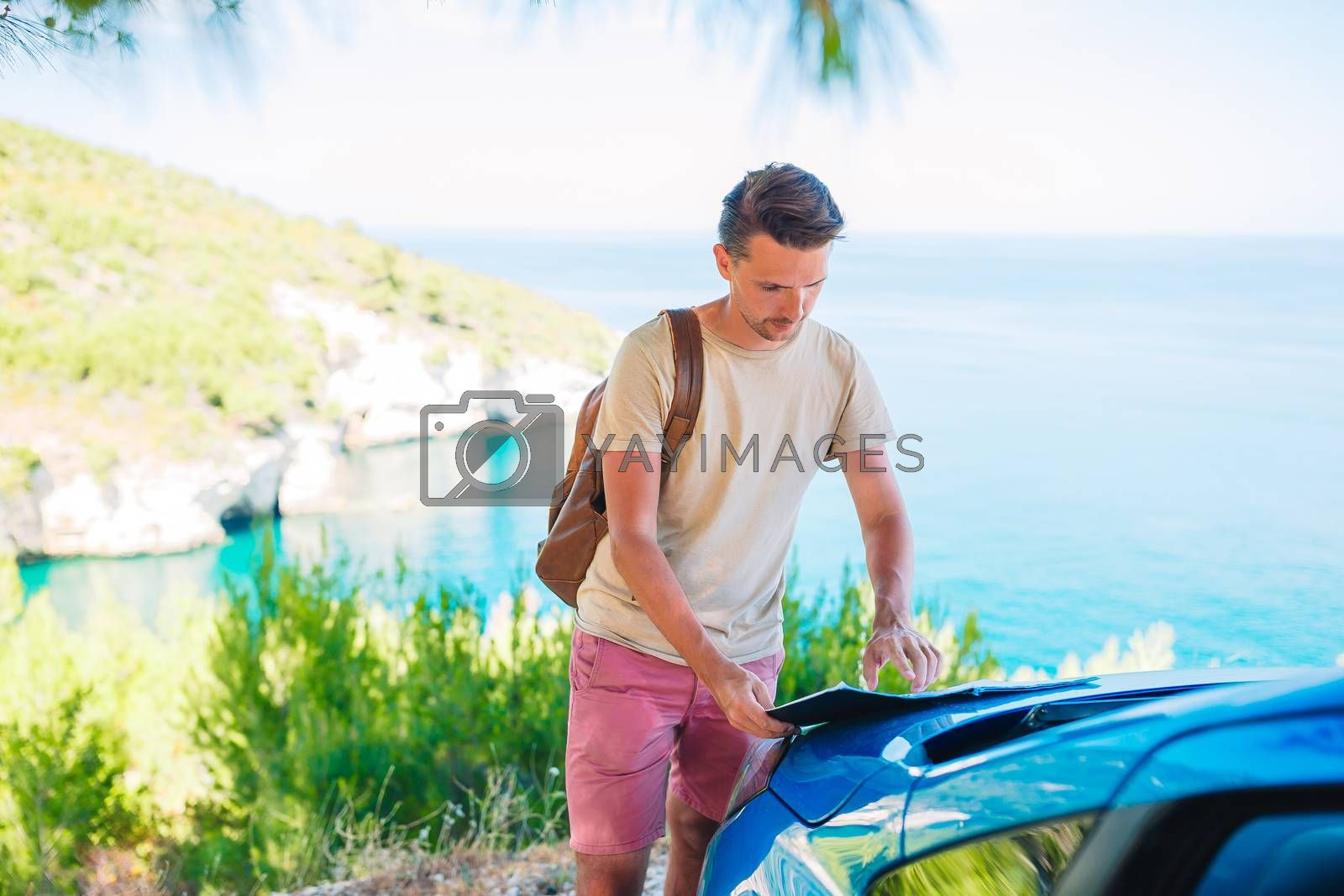 Young man with map travel by car on summer beach vacation