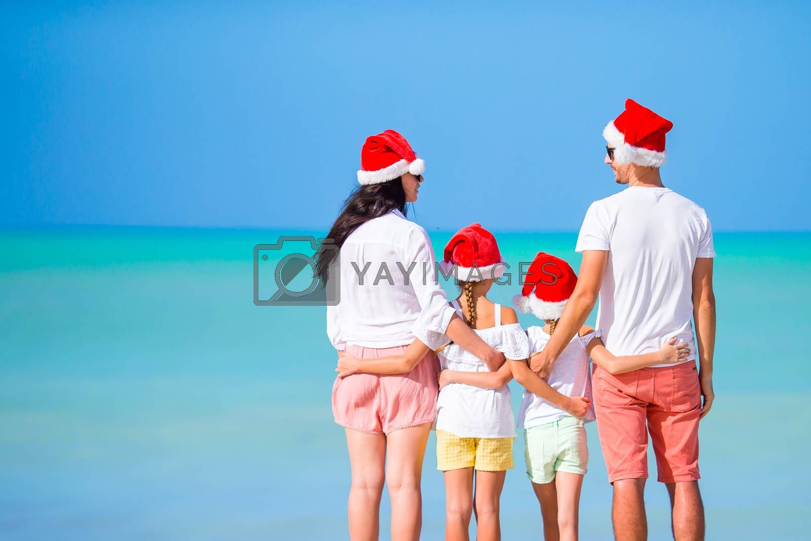 Happy family with two kids in Santa Hat on Christmas on the beach