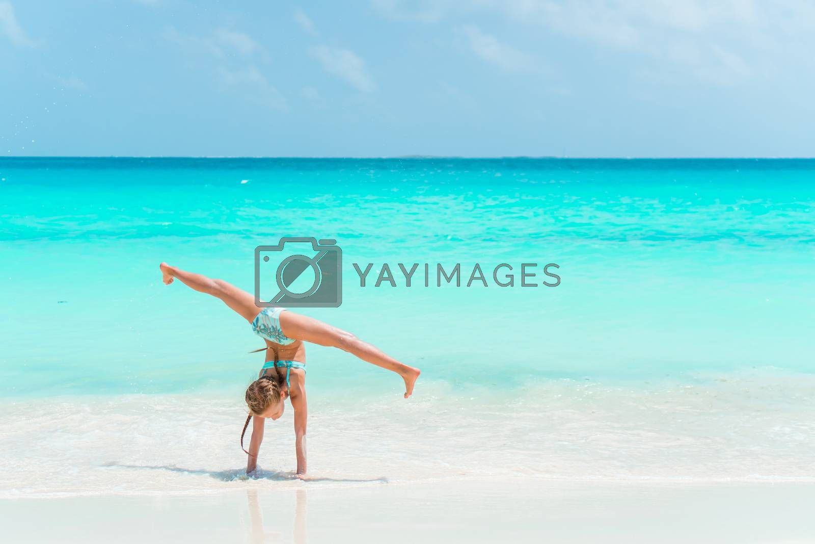 Active little girl at beach having a lot of fun. Sporty kid makes sporty exercises on the seashore