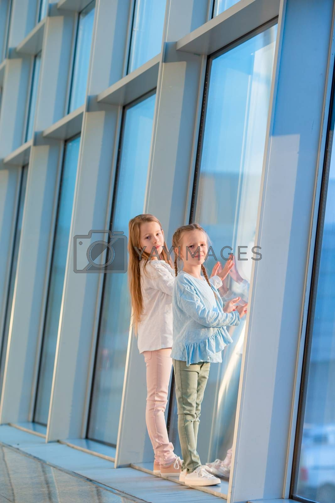 Little girls in airport near big window while wait for boarding