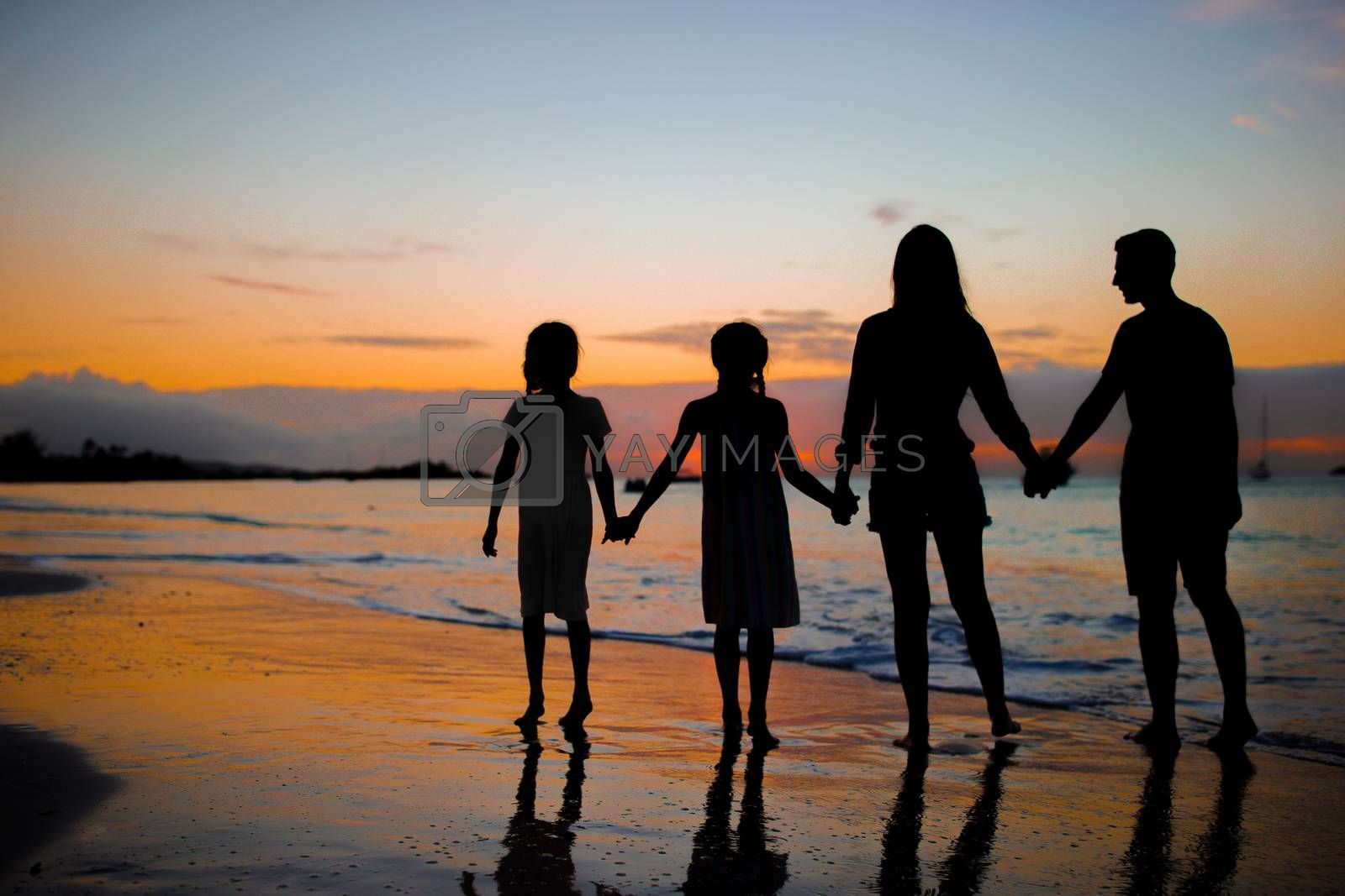 Family silhouette in the sunset on beach vacation