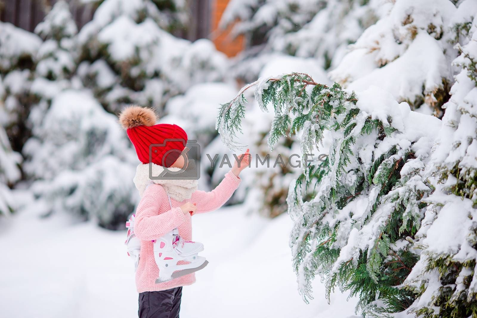 Portrait of happy little girl going to skate in winter snow day outdoors. Beautiful kid in red hat and white scarf