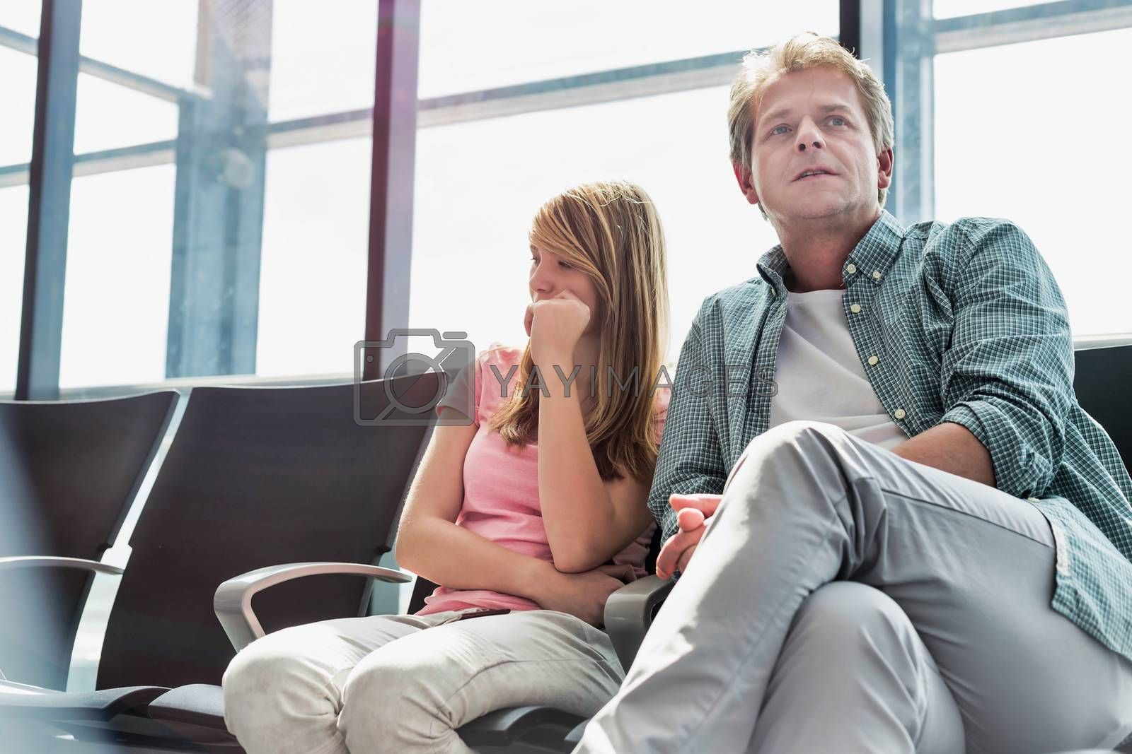 Mature man sitting with his daughter while waiting for their flight in airport