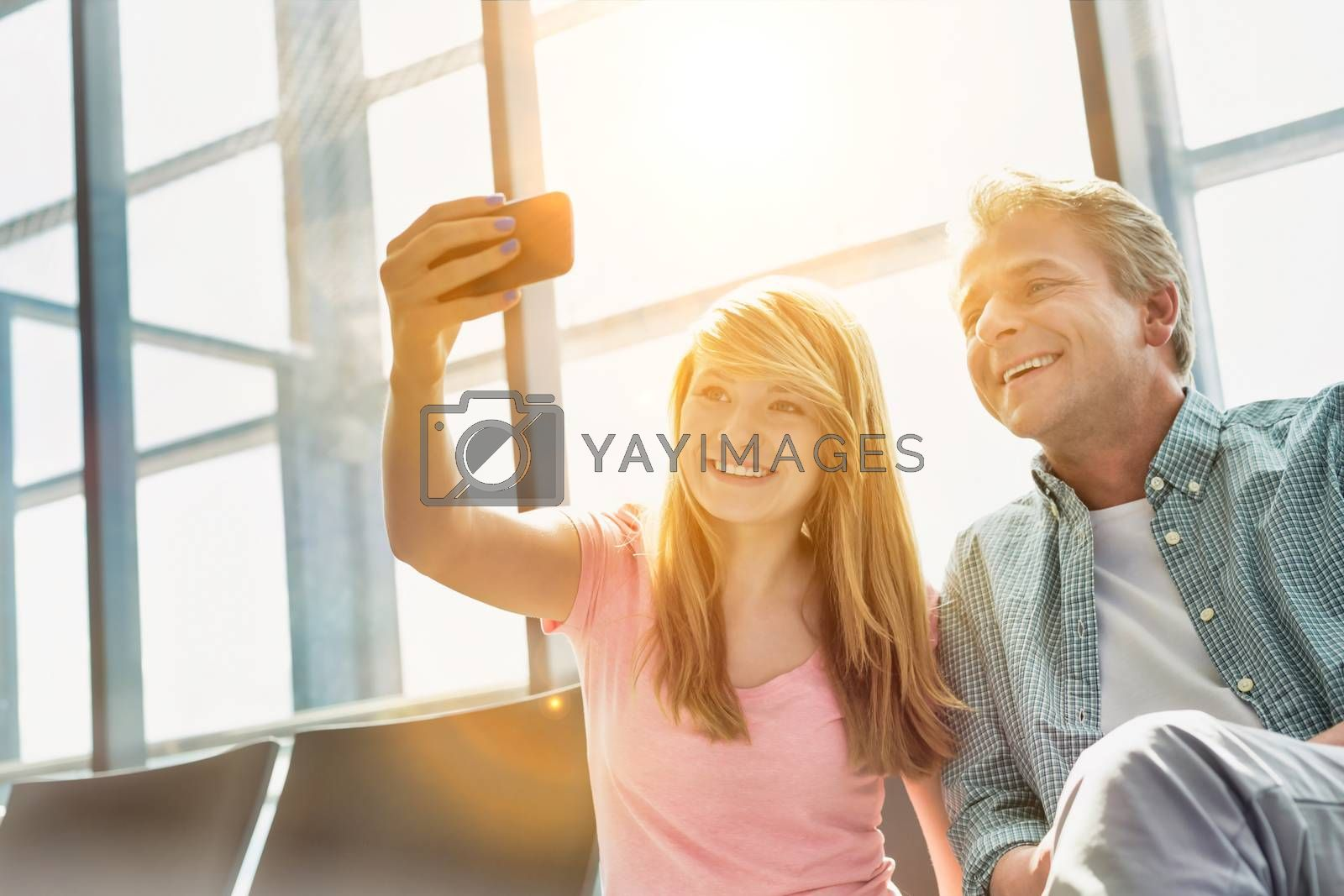 Portrait of young beautiful teenage girl taking selfie with her father in airport