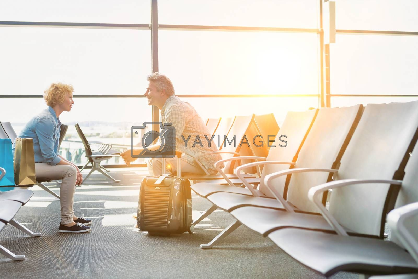 Mature couple sitting while waiting for their flight in airport