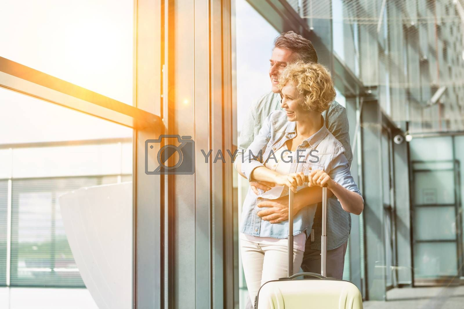 Mature man hugging his wife from behind while looking through the window in airport