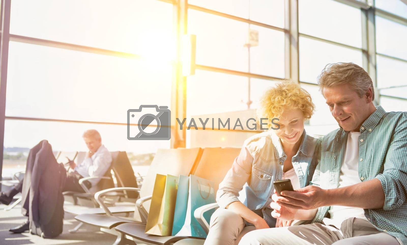 Portrait of mature man showing smartphone to his wife while waiting for their flight in airport