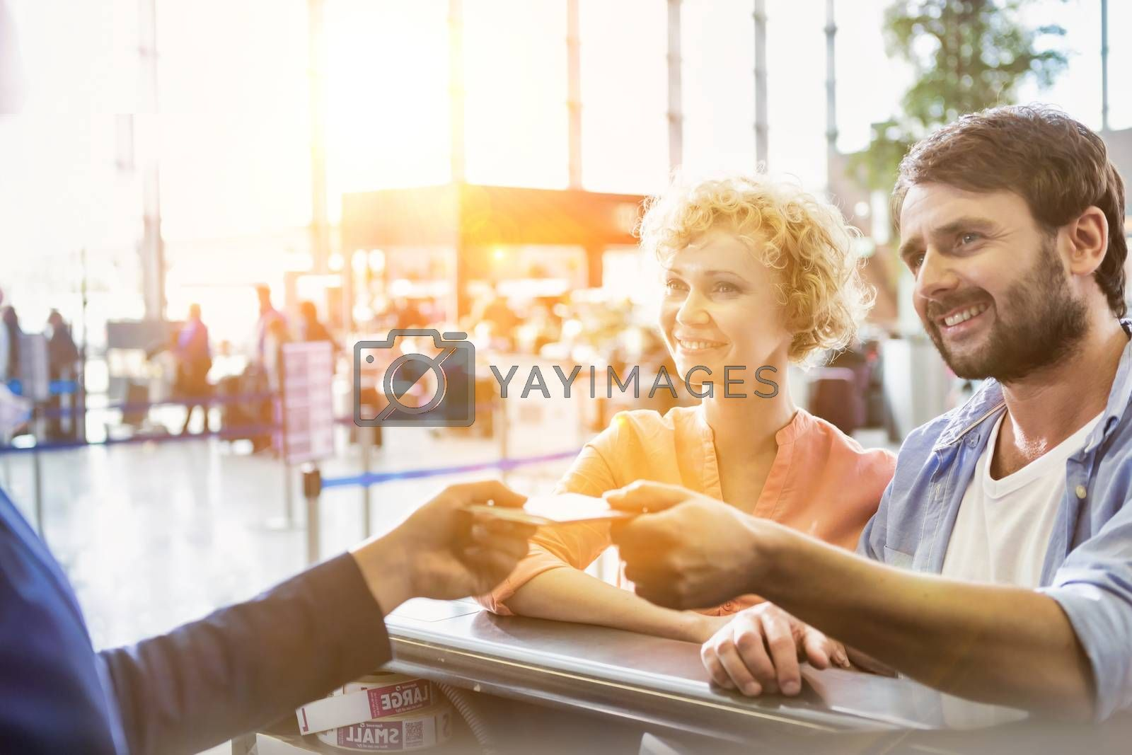 Portrait of man giving passport to passenger service agent to get his boarding pass in airport
