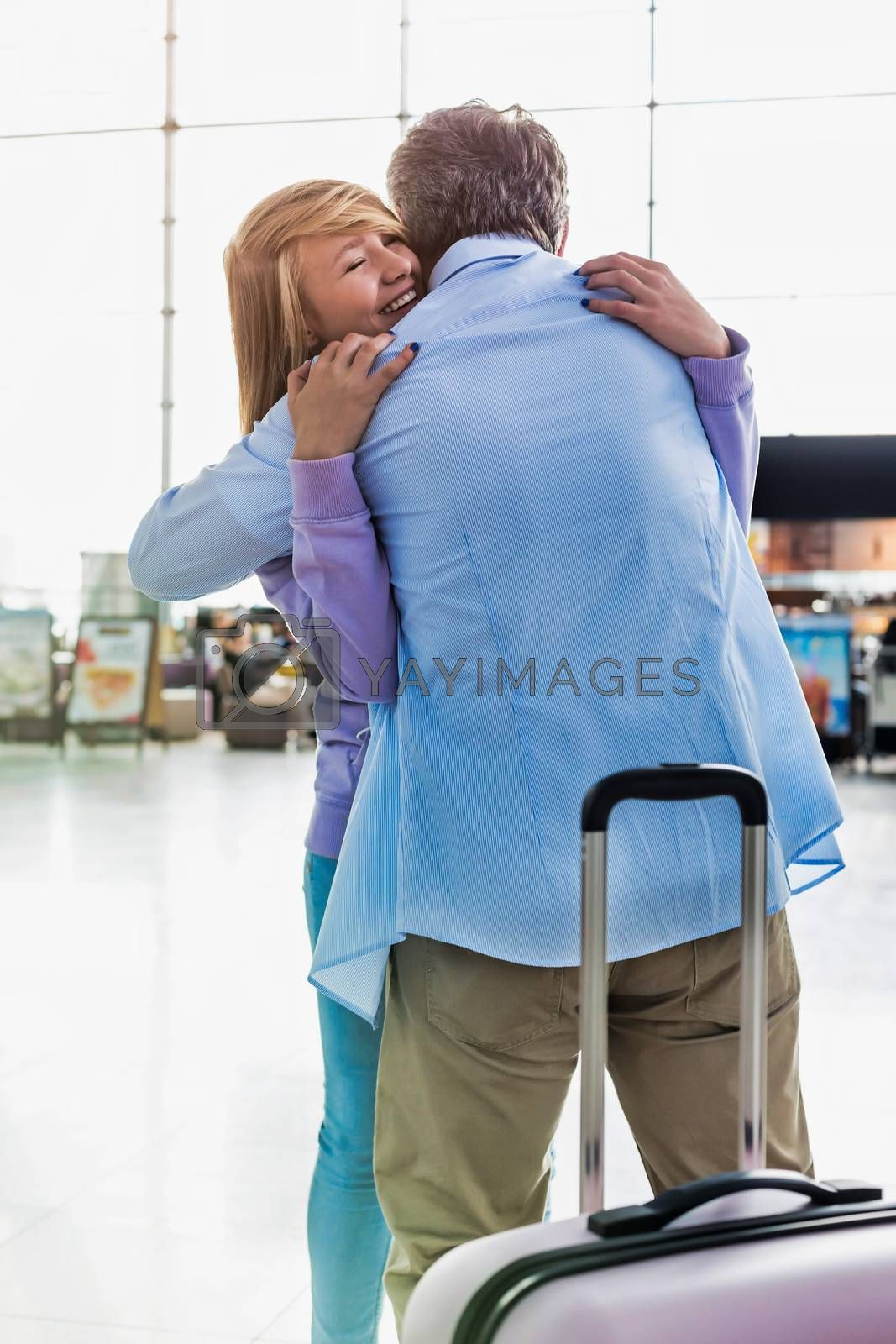 Portrait of mature man reuniting with his daughter in airport
