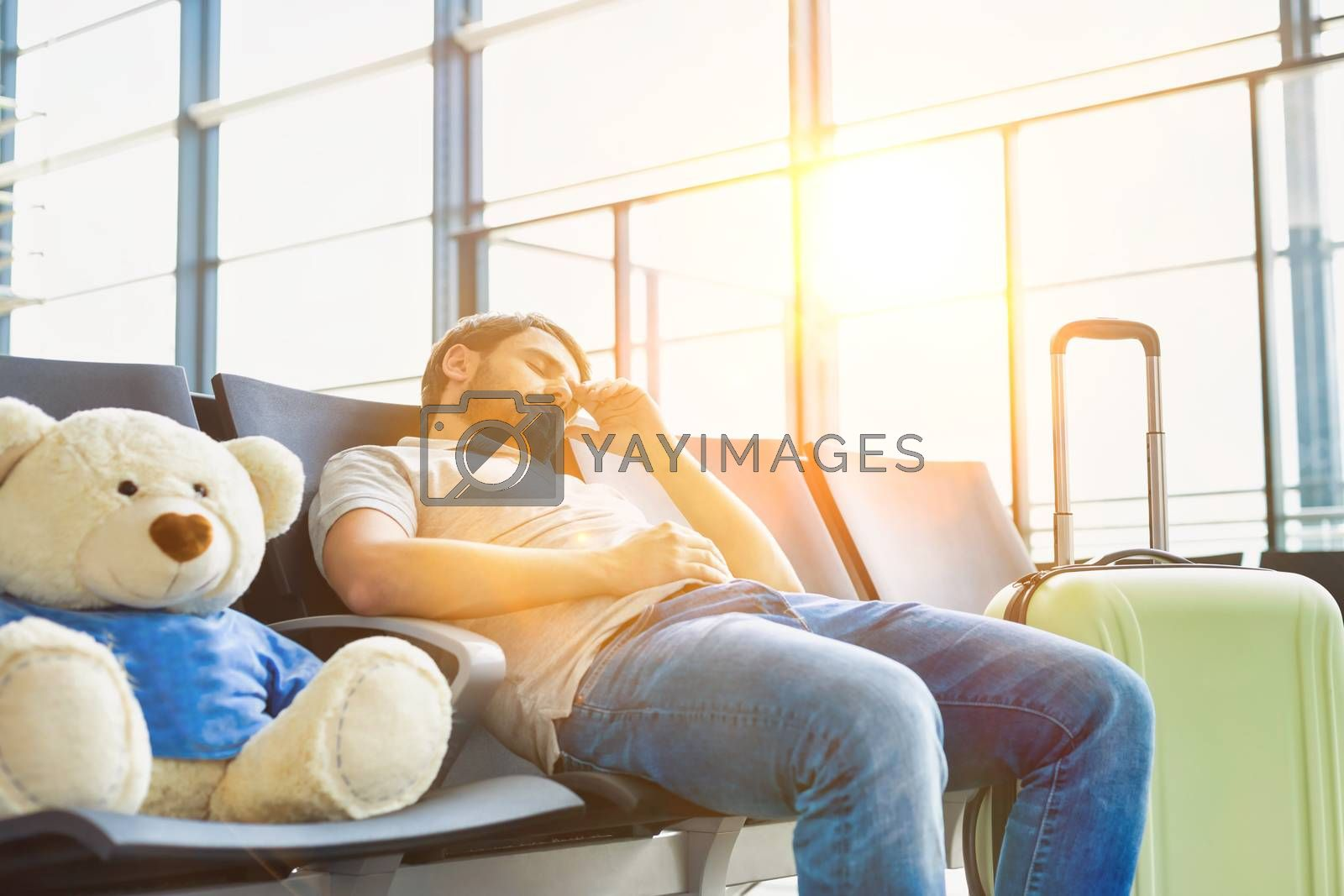 Portrait of man sleeping and lying on chair while waiting for his flight in airport