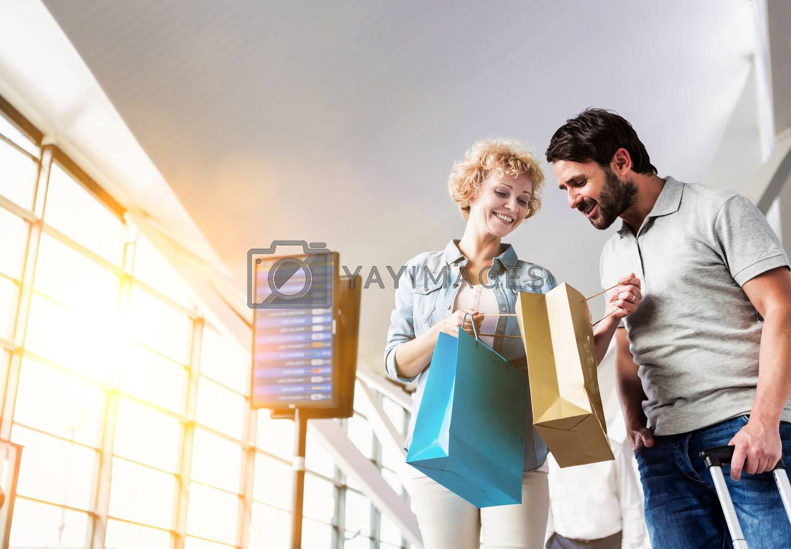 Portrait of mature woman showing present she bought in duty free with her husband at airport