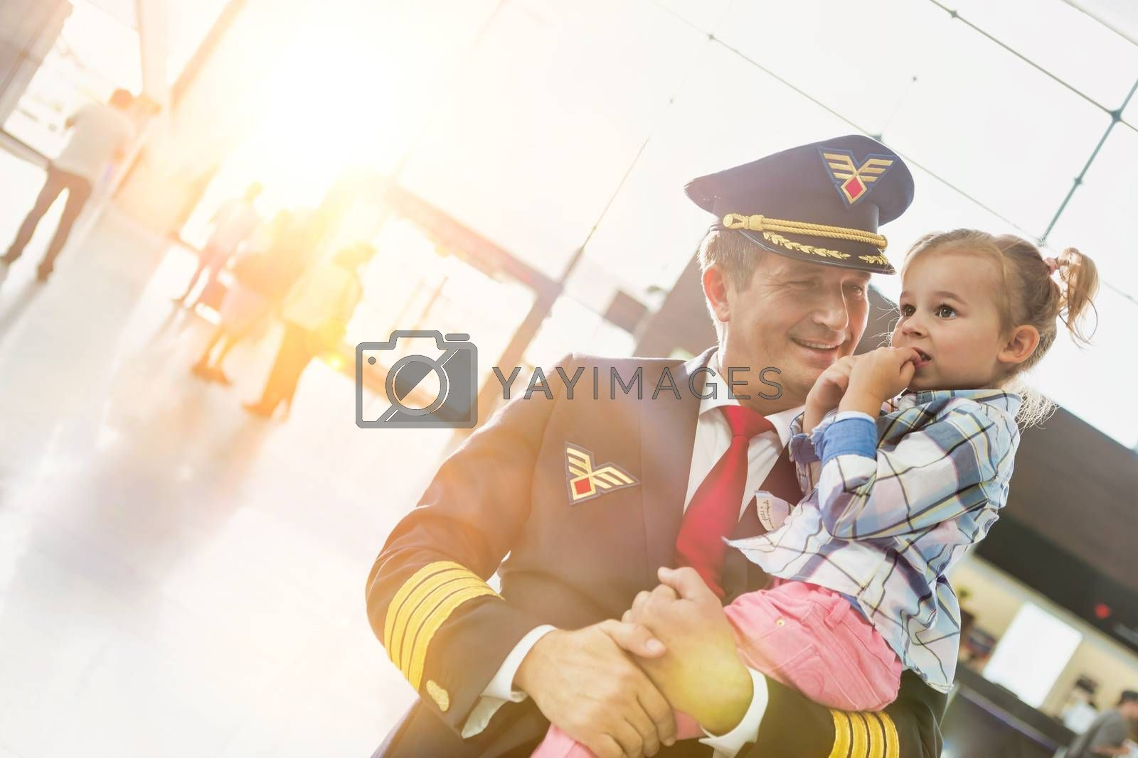 Portrait of mature pilot carrying cute little child in airport