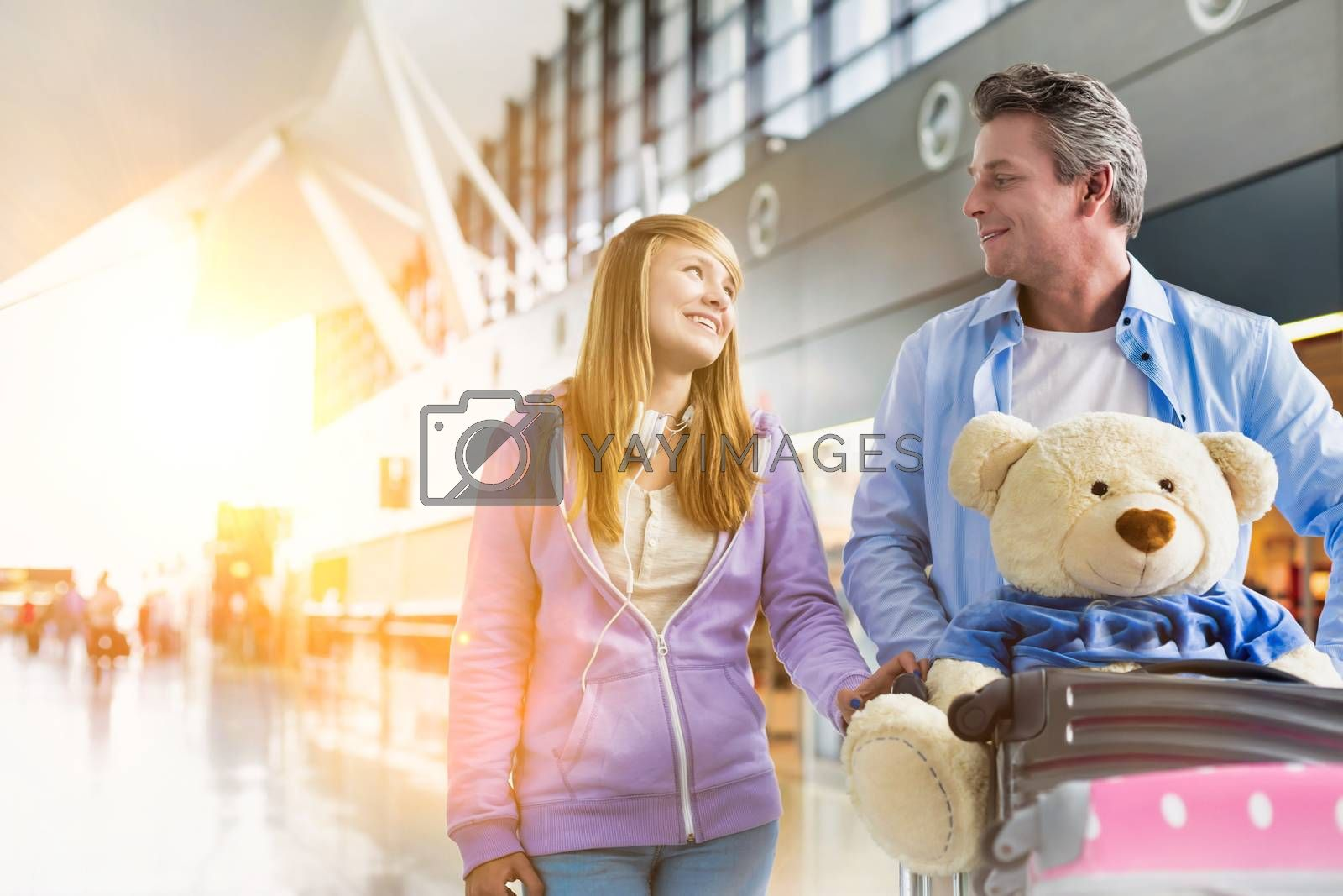 Portrait of mature man pushing baggage cart while walking with her daughter in airport with lens flare