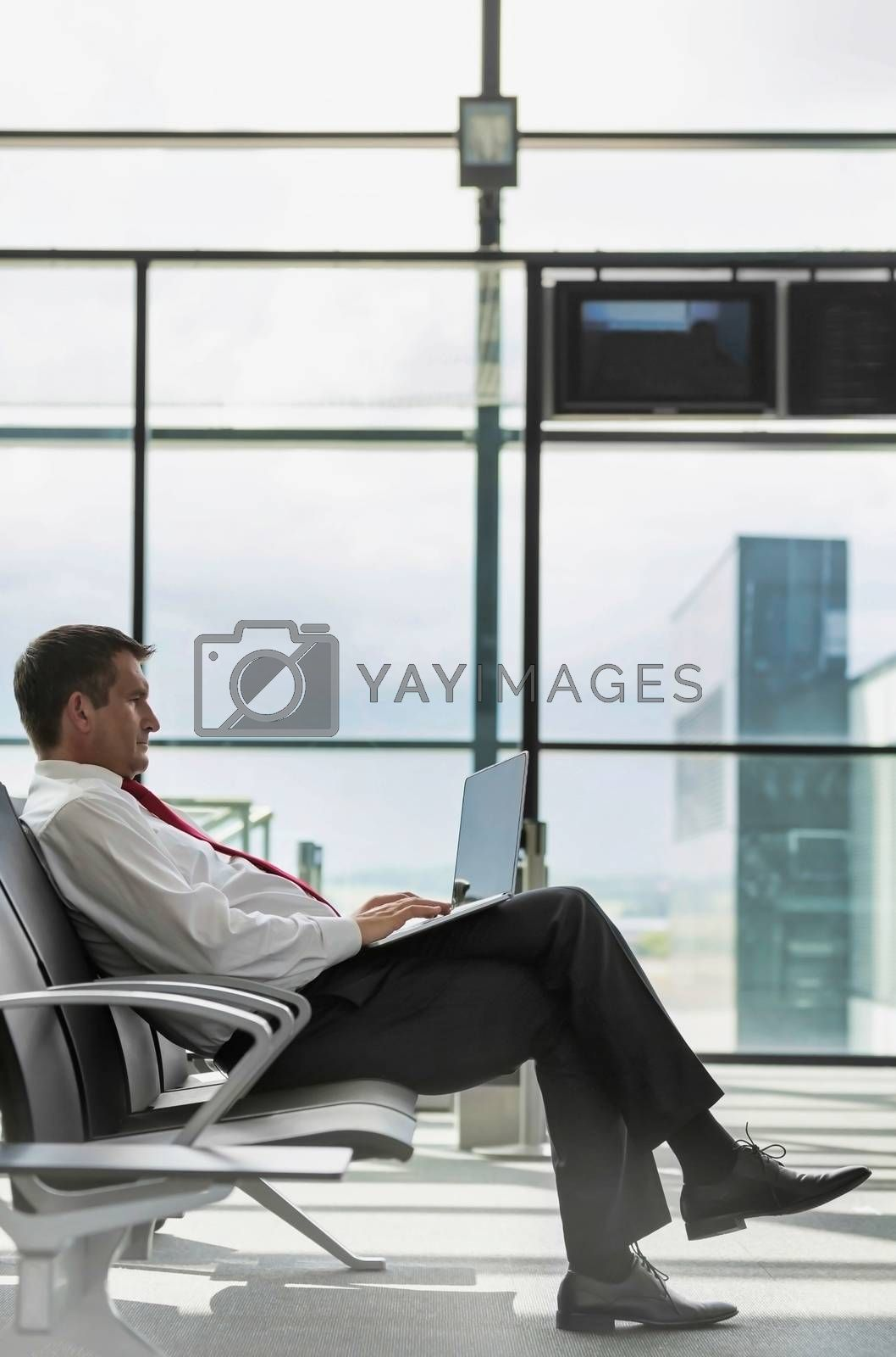 Portrait of mature businessman working on his laptop while sitting and waiting for flight in airport