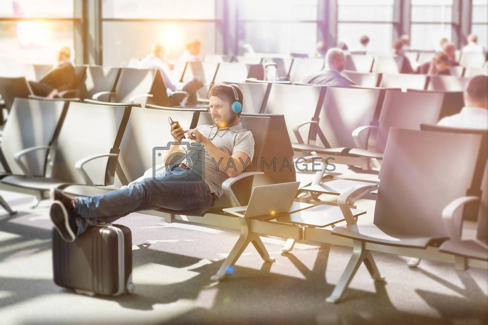 Portrait of man using smartphone with headphones on while waiting for boarding in airport