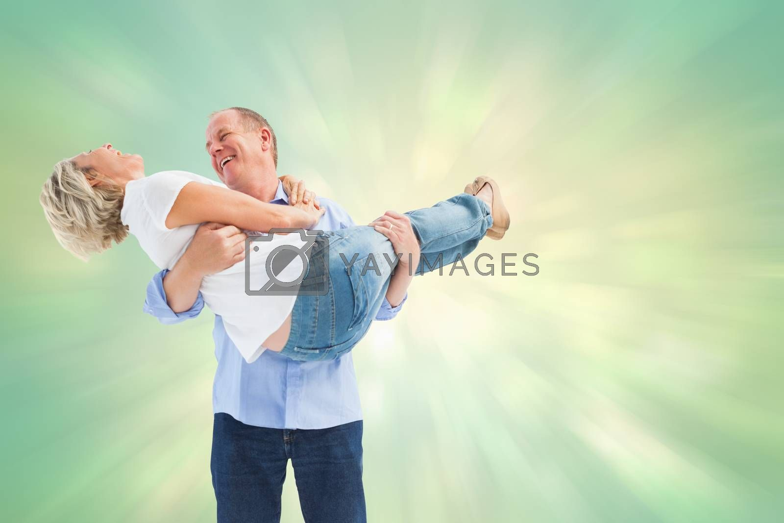 Mature man carrying his laughing partner against green abstract light spot design