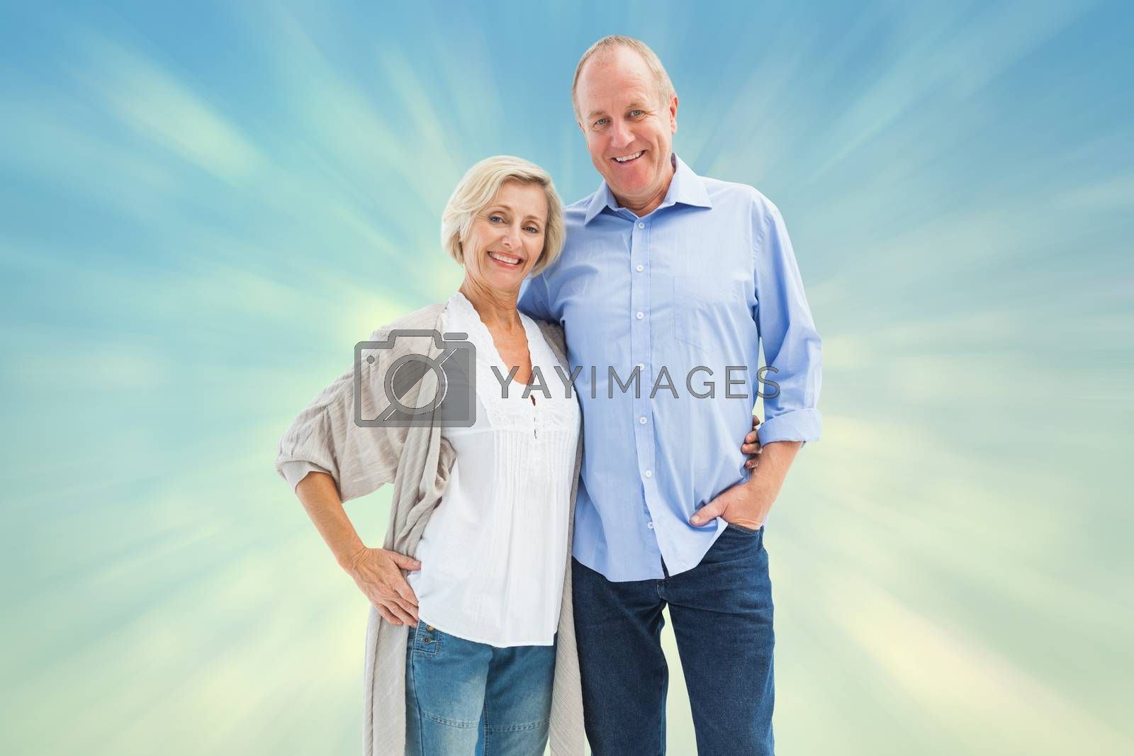 Happy mature couple hugging and smiling against blue abstract light spot design