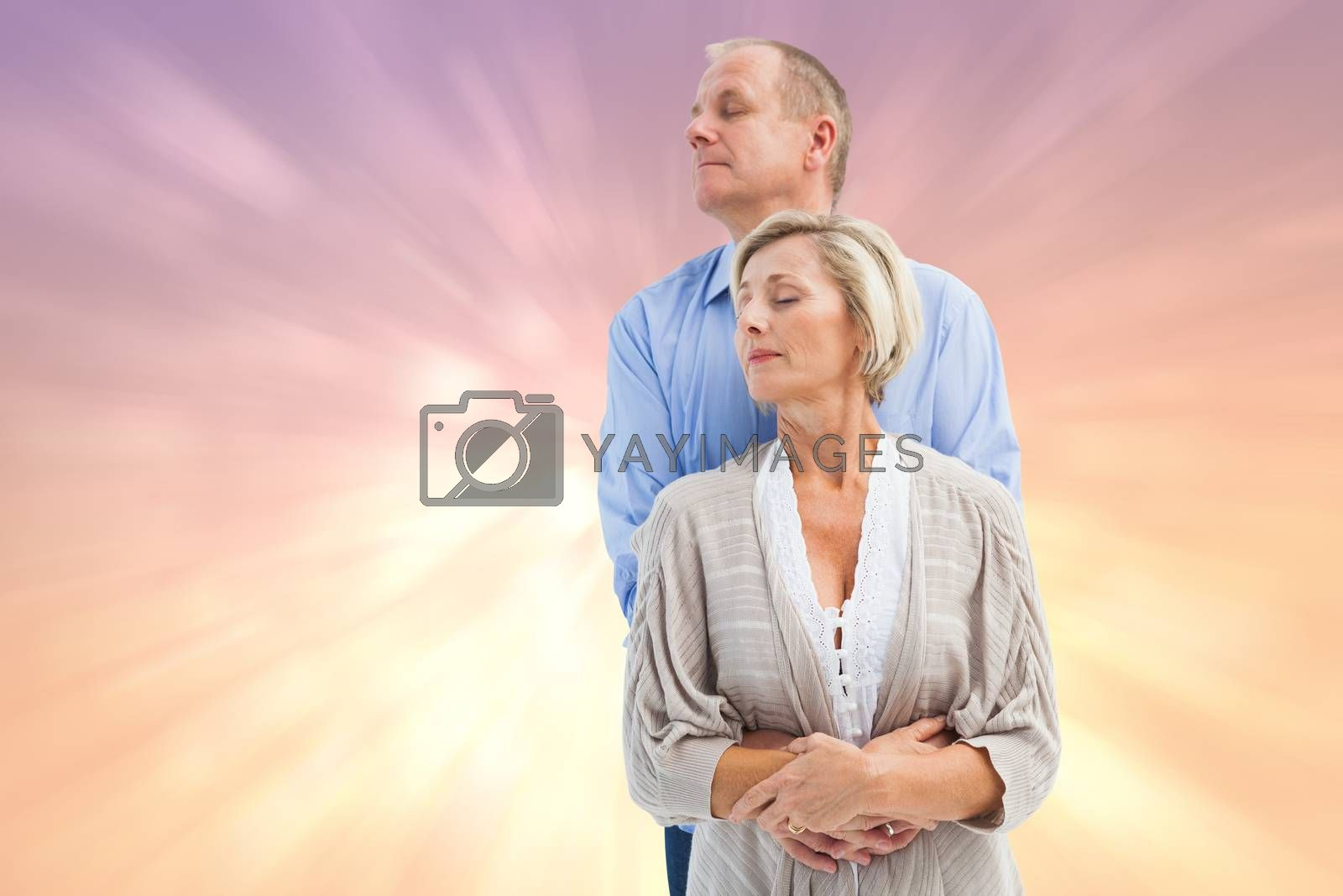 Happy mature couple embracing with eyes closed against pink abstract light spot design