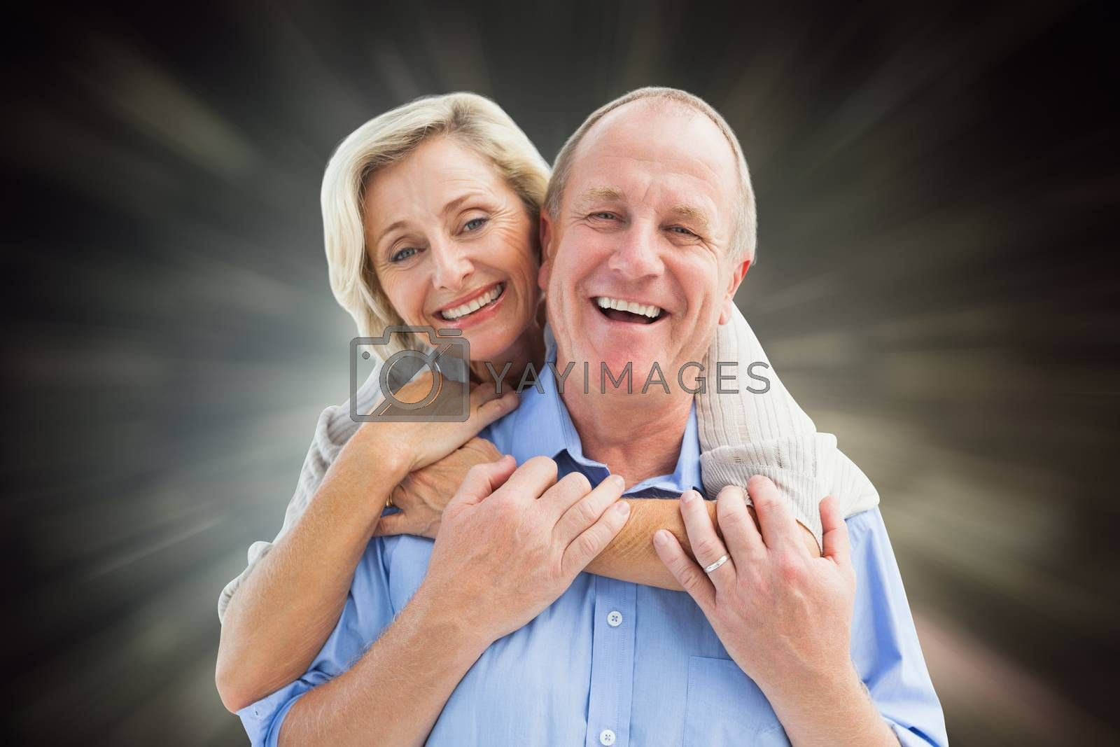 Happy mature couple embracing smiling at camera against black abstract light spot design
