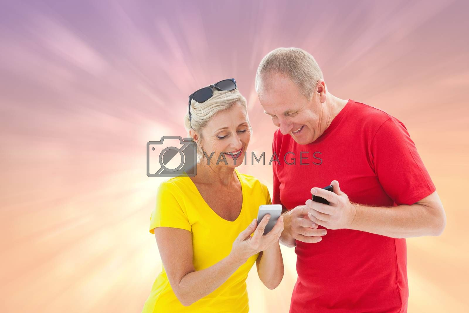 Happy mature couple looking at smartphone together against pink abstract light spot design