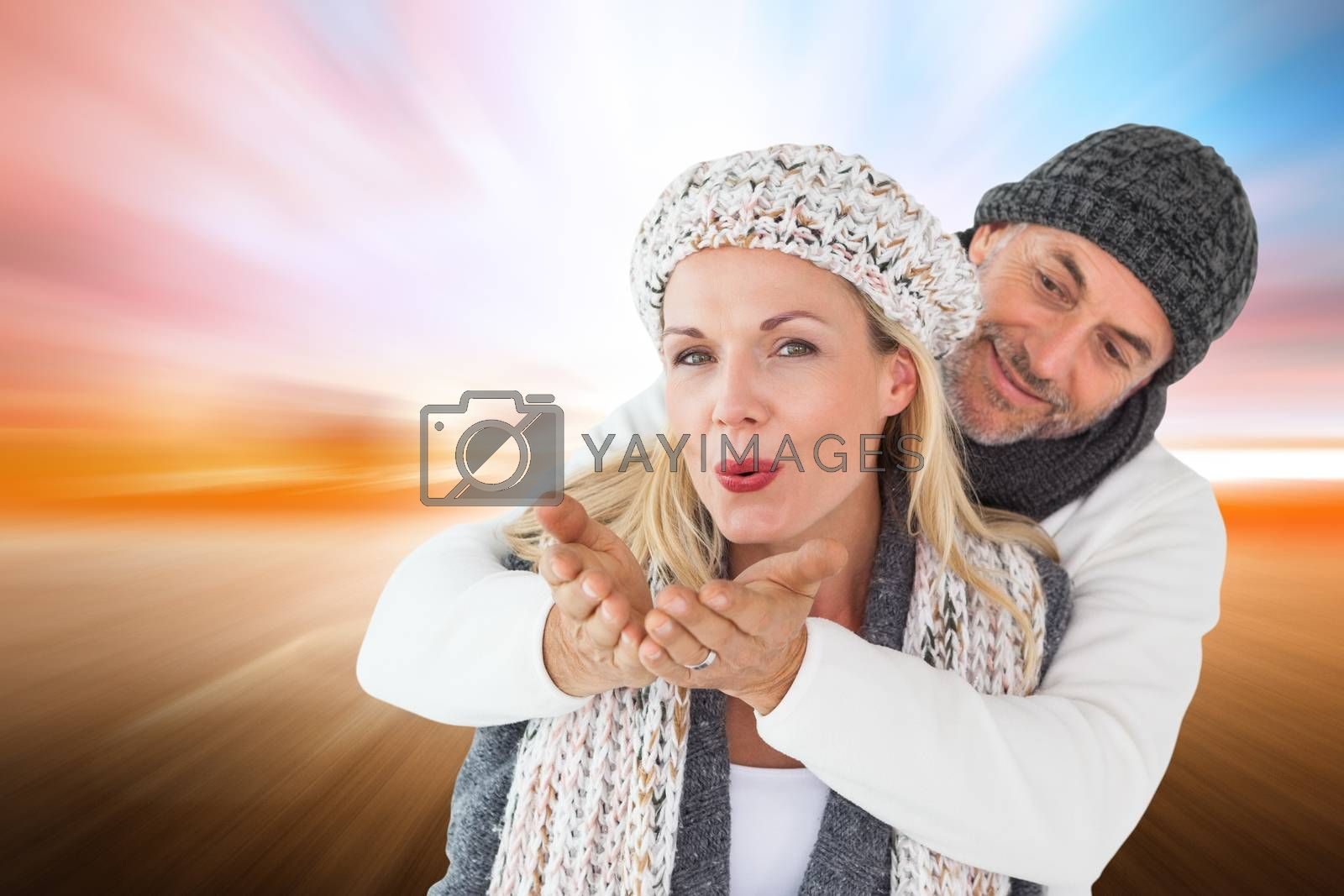 Smiling couple in winter fashion posing against field with light wave