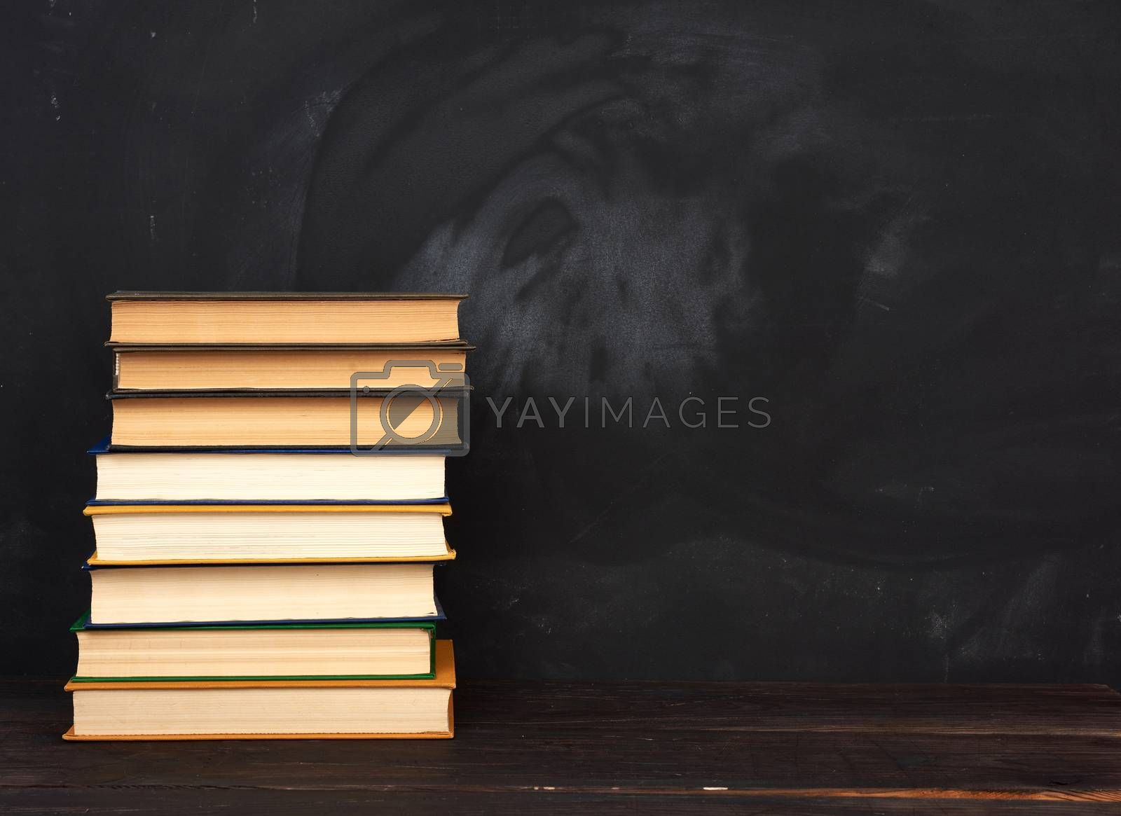 stack of various hardback books on the background of an empty black chalk board, place for text, back to school