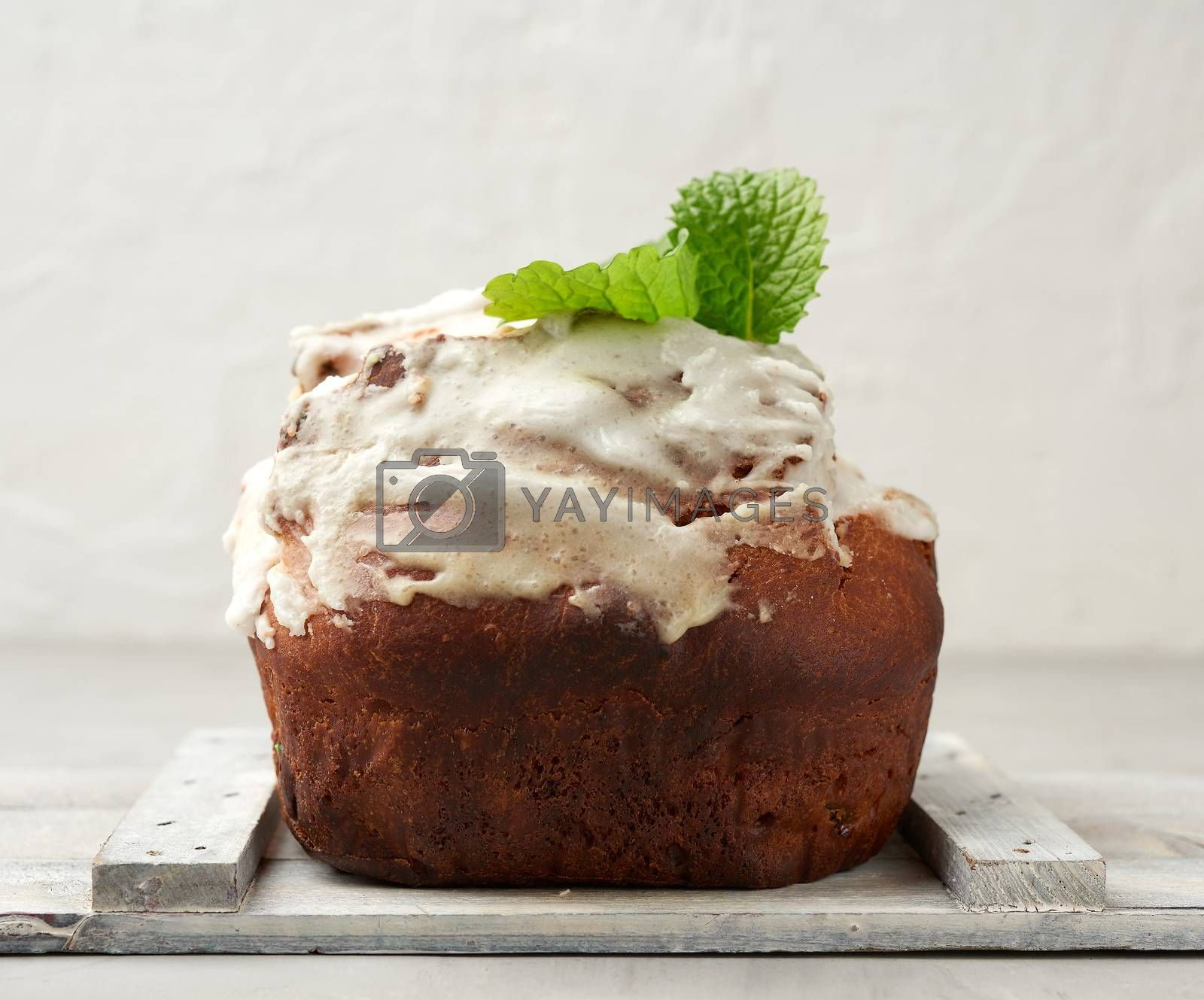 baked Easter cake with white lemon glaze on a white wooden board by ndanko