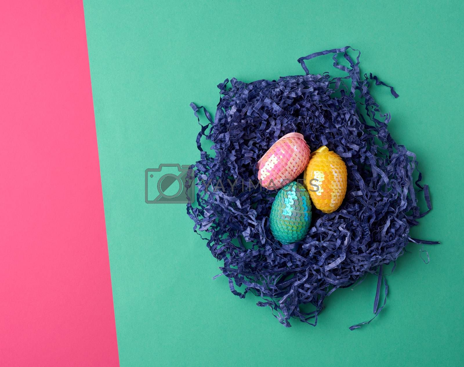 decorative Easter eggs from sequins lie in a nest of strips of p by ndanko