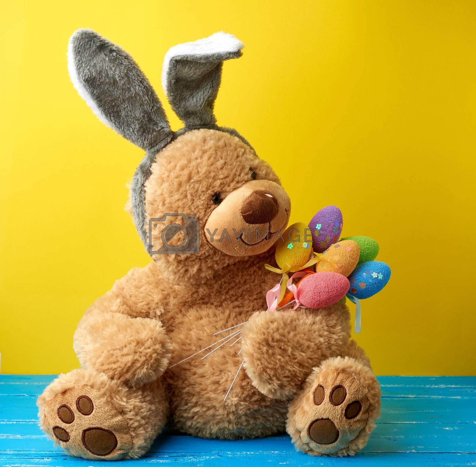 big cute brown teddy bear holding colorful Easter eggs, wearing  by ndanko