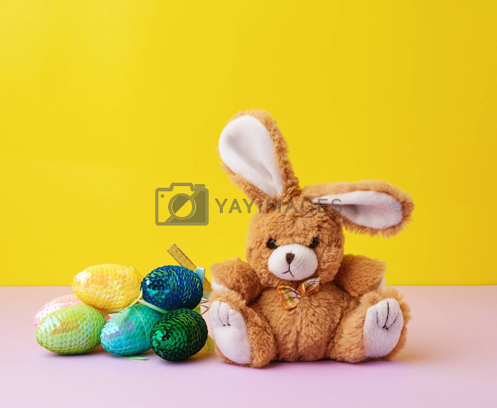 cute rabbit toy and decorative Easter eggs with sequins on a yel by ndanko
