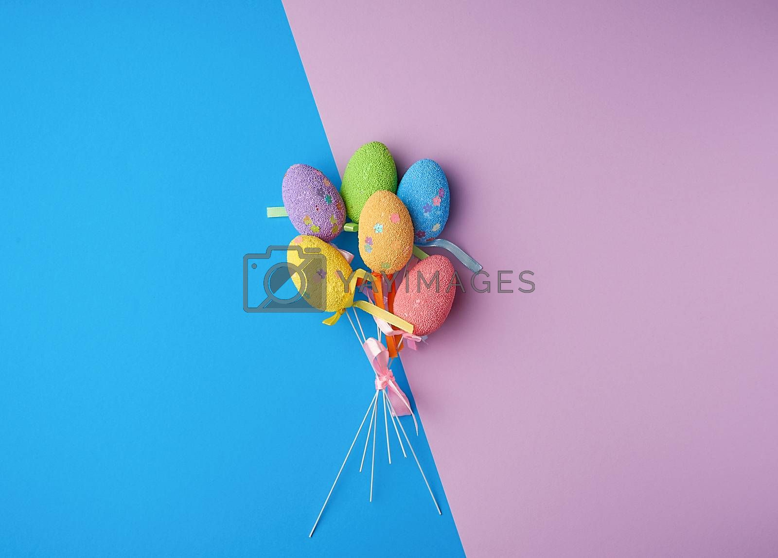 multi-colored decorative Easter eggs on sticks on a blue lilac b by ndanko