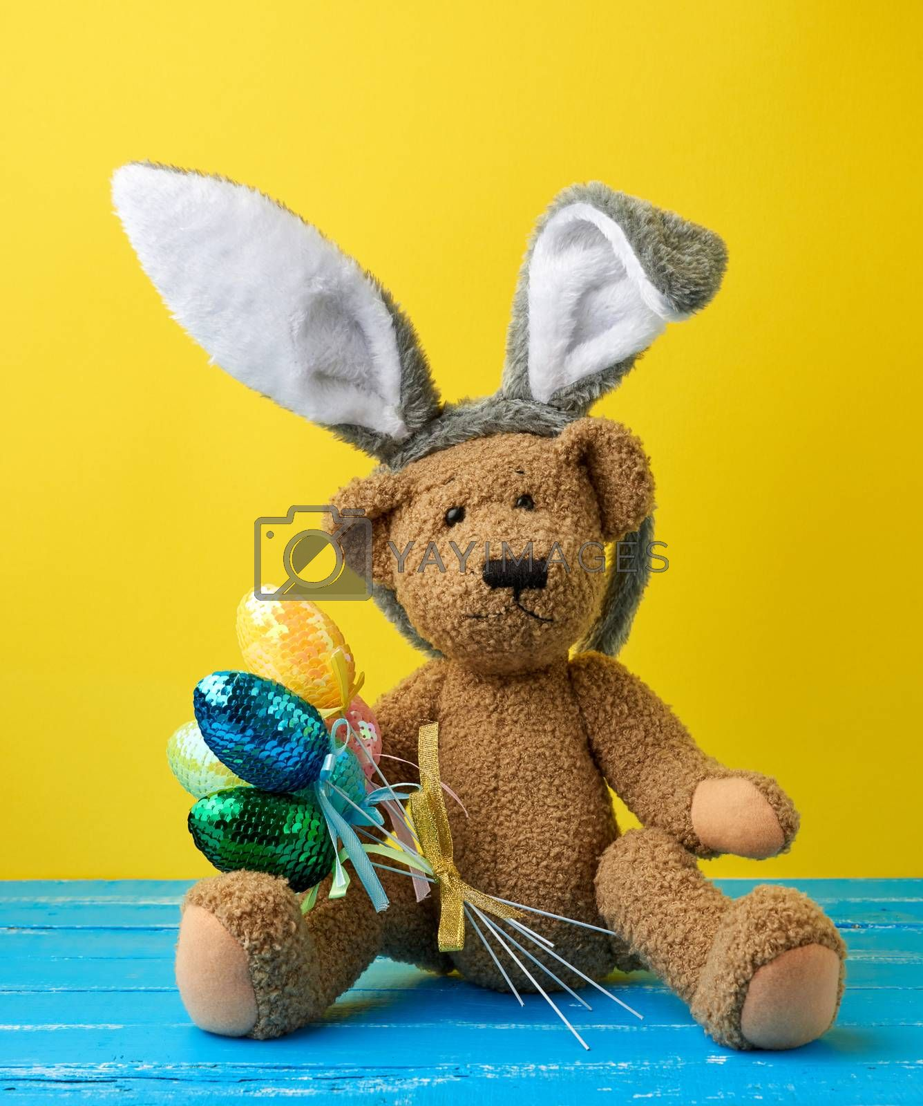 cute brown teddy bear holding colorful Easter eggs, wearing a ra by ndanko