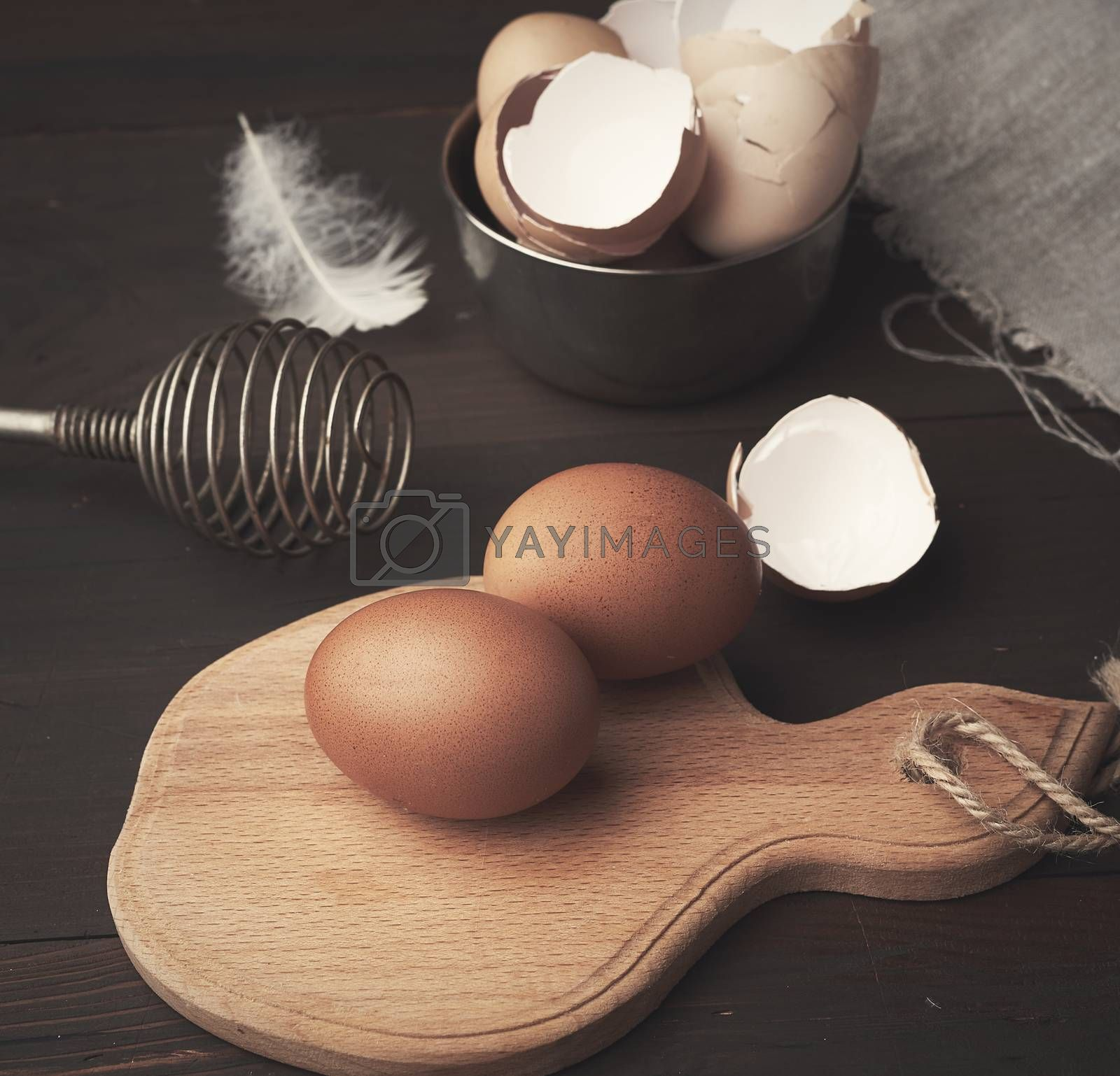brown whole chicken eggs on a wooden board by ndanko