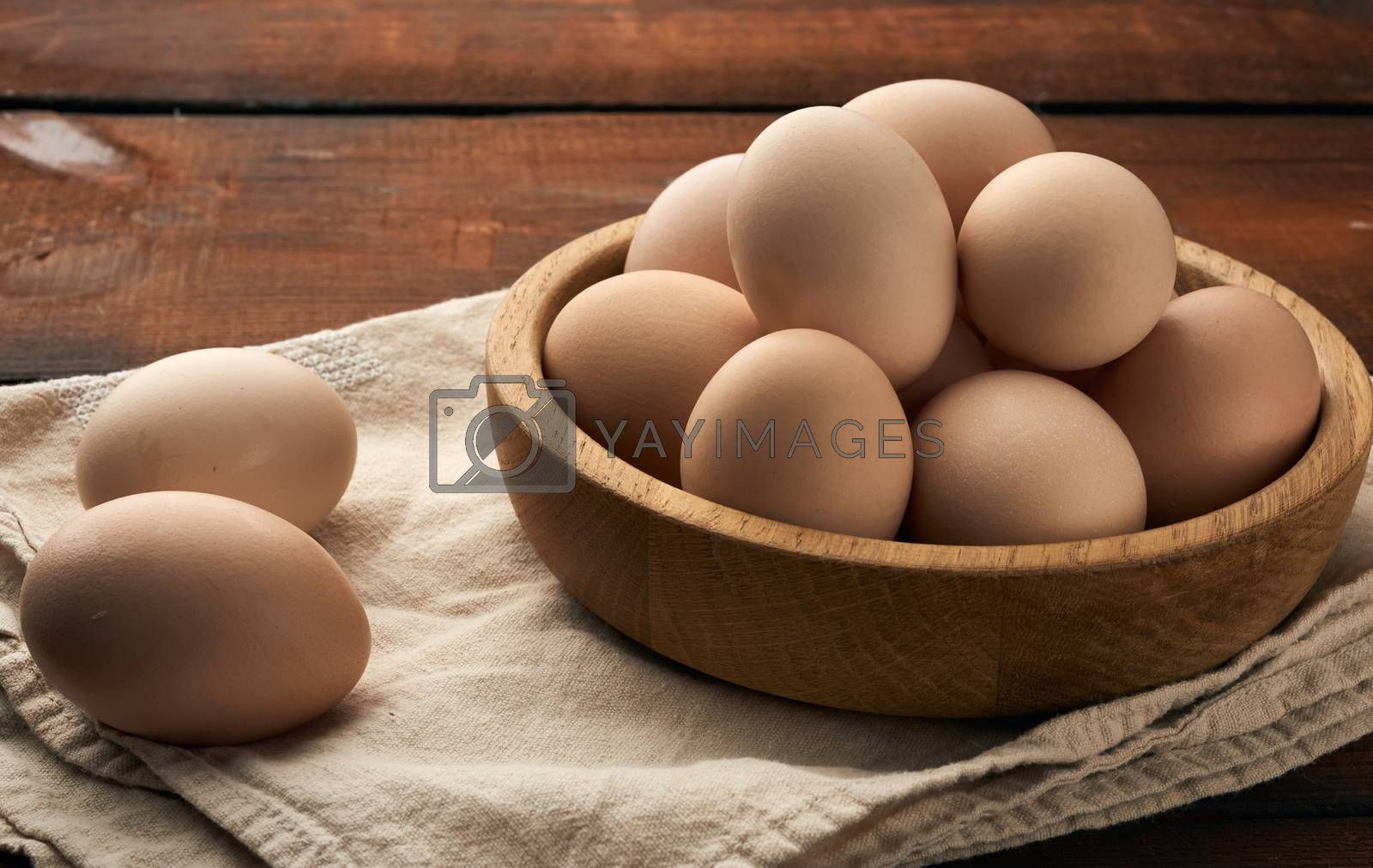 raw brown chicken eggs in a wooden plate on the table by ndanko