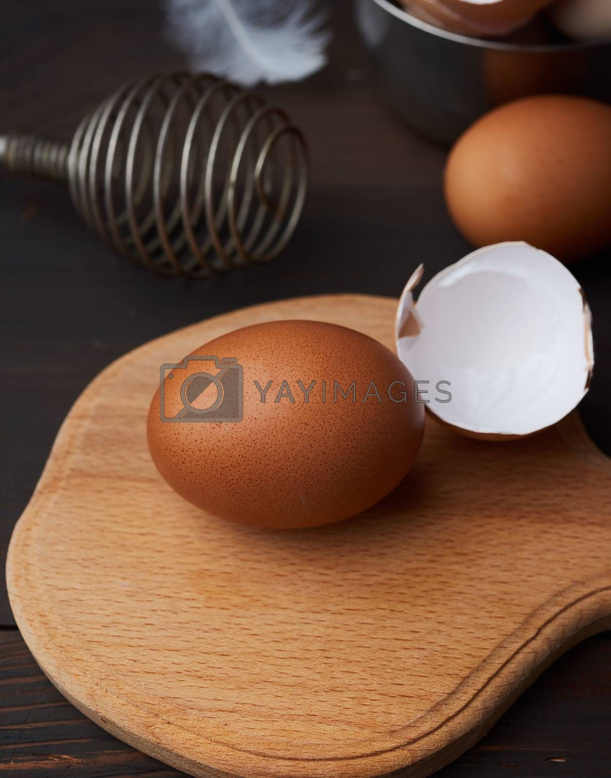 brown whole chicken eggs on a wooden board, behind a whisk for w by ndanko