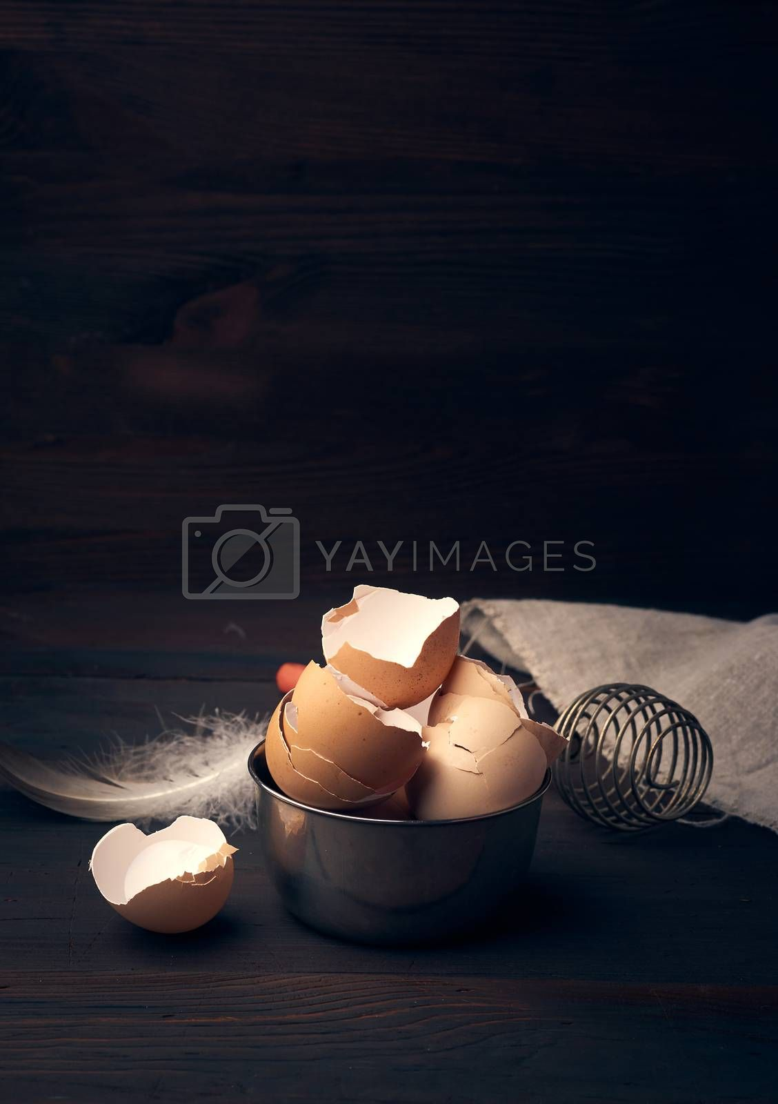 brown raw chicken shell in an iron bowl on a wooden table by ndanko