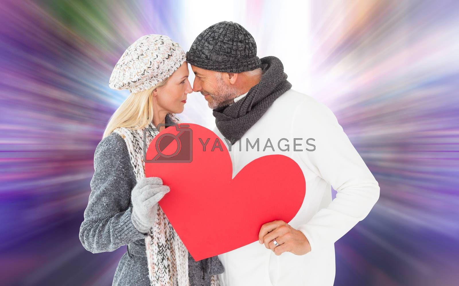 Smiling couple in winter fashion posing with heart shape against glittering screen in urban setting