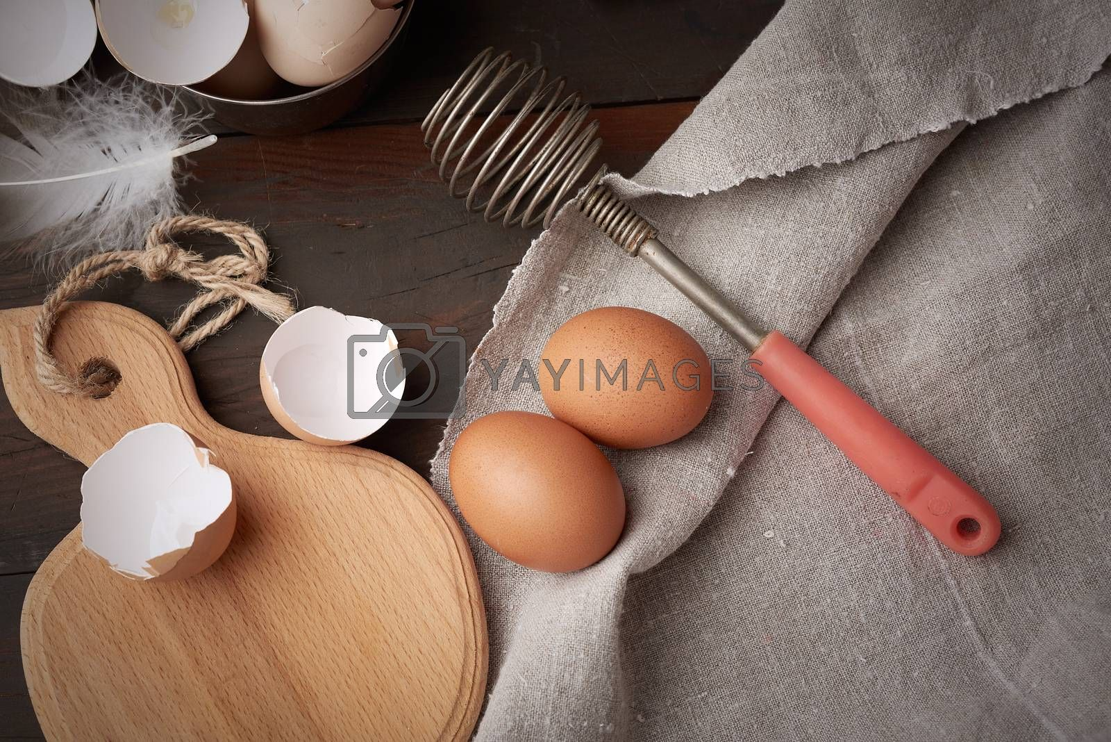 brown raw chicken eggs, shells, cutting board and hand-held whis by ndanko