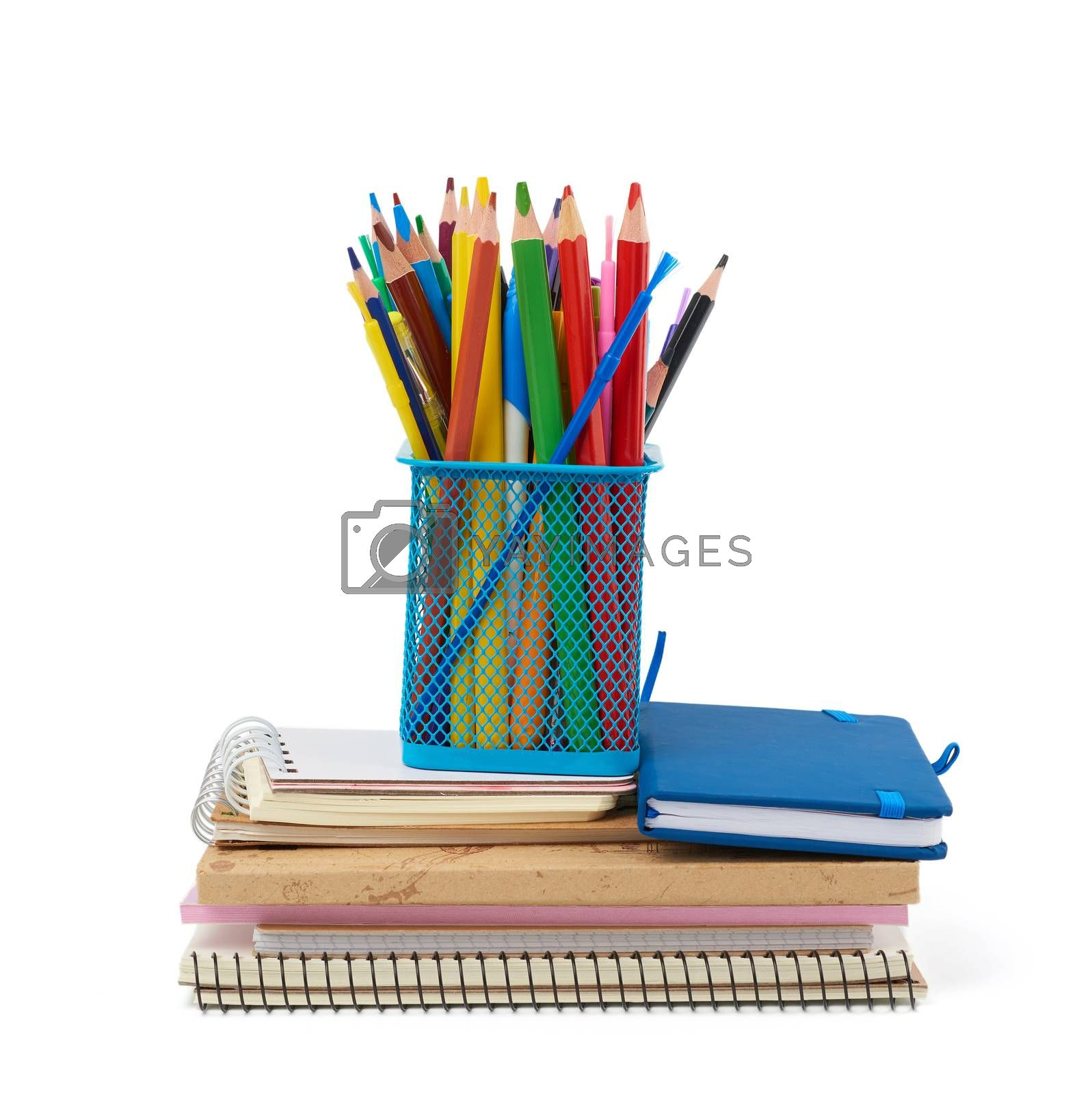 wooden multi-colored pencils, plastic pens and a stack of paper notebooks are isolated on a white background, stationery