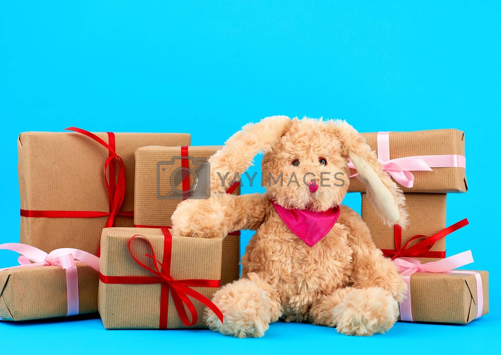 cute little brown plush rabbit and a stack of boxes wrapped in b by ndanko