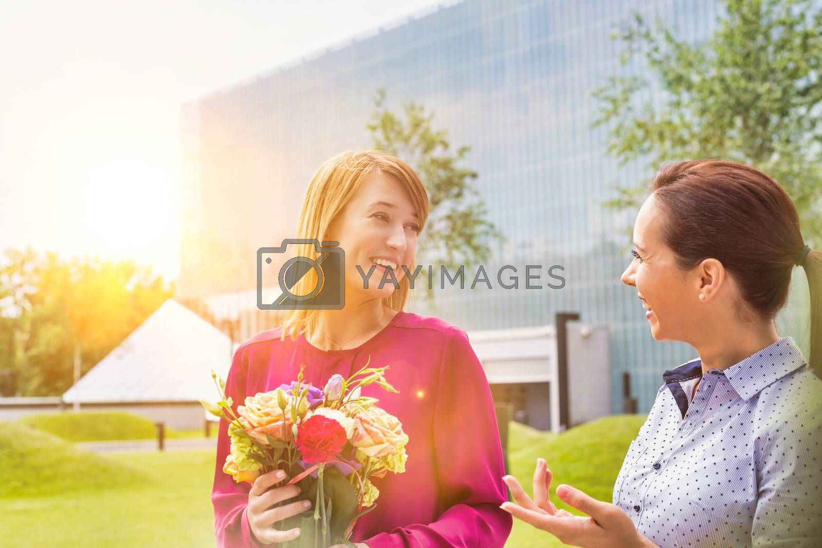 Businesswoman holding boquet of flowers while talking to her friend