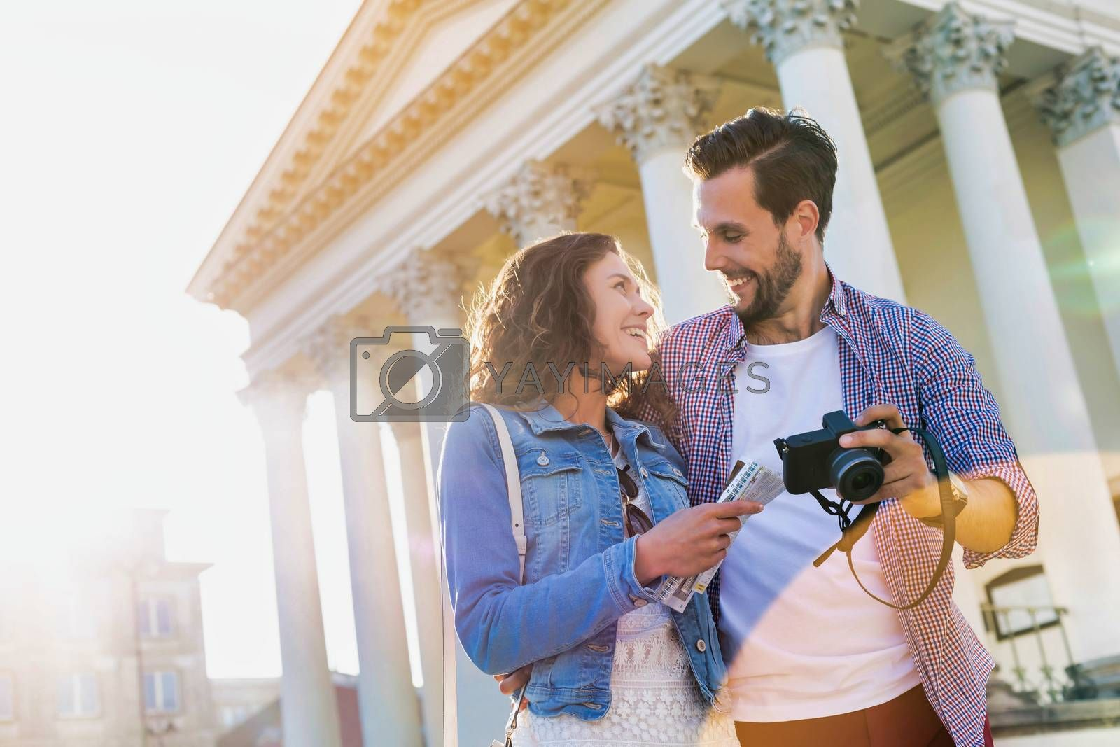Portrait of man showing pictures on camera to his girlfriend