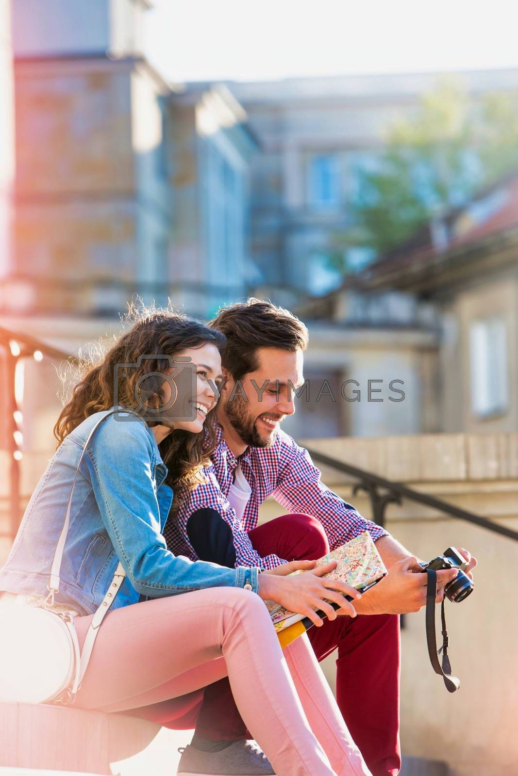 Portrait of man looking on camera while his girlfriend is holding city map