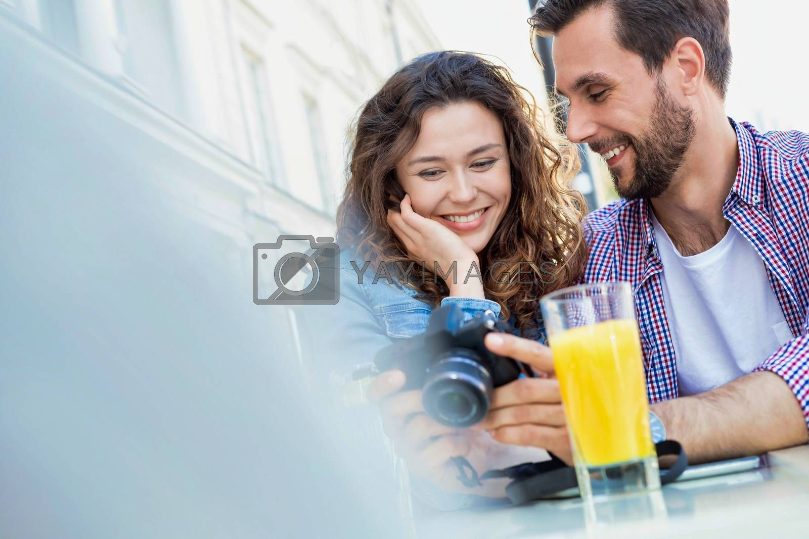 Portrait of young attractive couple looking at their pictures on camera