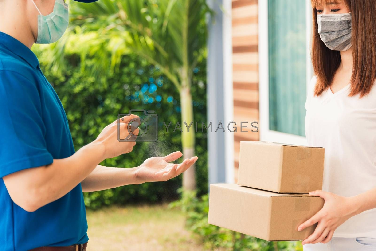 Asian delivery express courier young man use spray sterilize before giving boxes to woman customer receiving both protective face mask, under curfew quarantine pandemic coronavirus COVID-19
