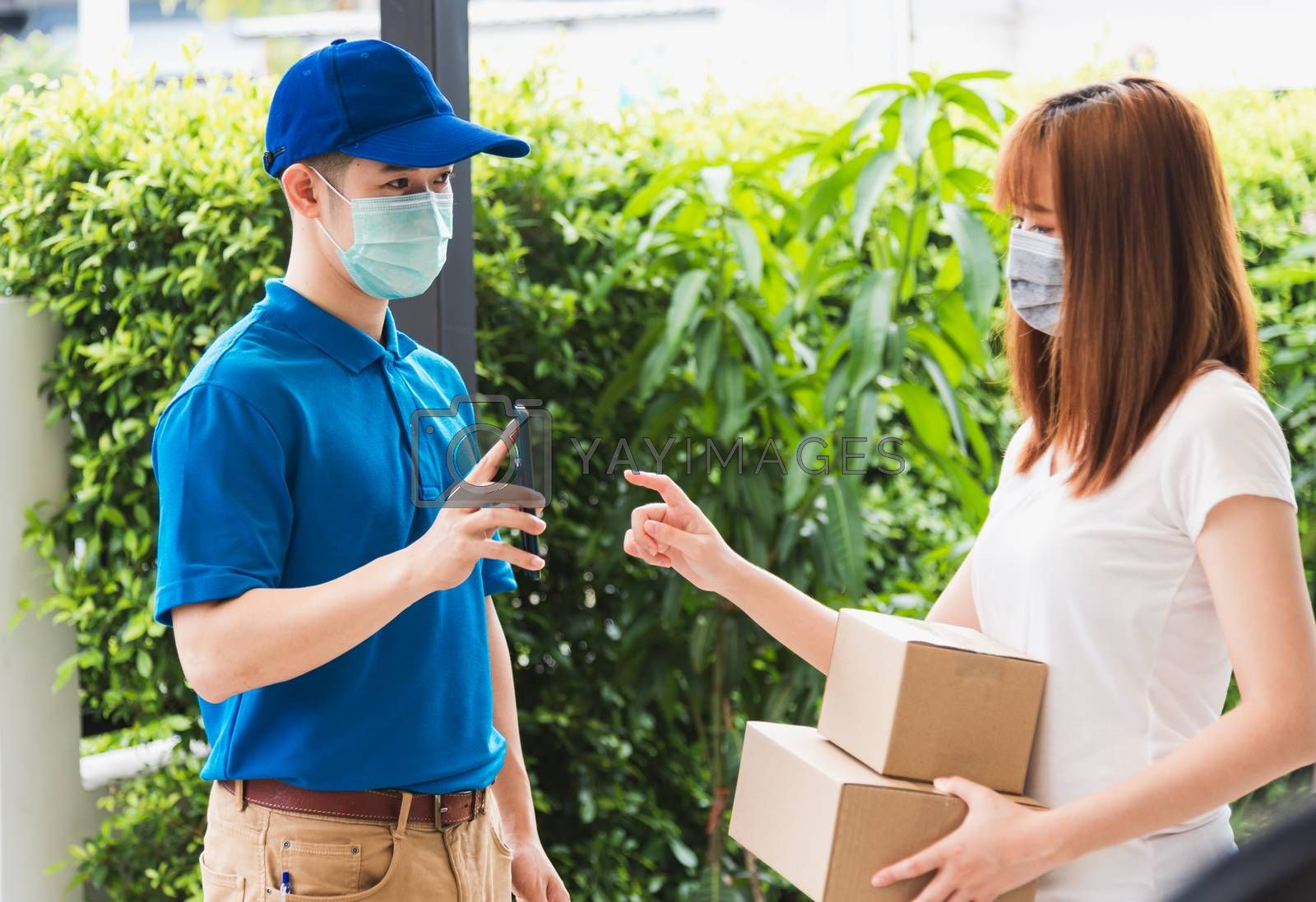 Asian delivery express courier young man giving parcel boxes to woman customer signature for receiving on mobile phone both protective face mask, under curfew quarantine pandemic coronavirus COVID-19