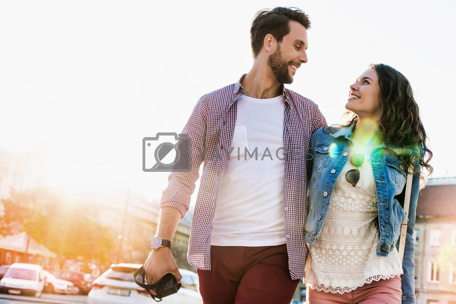 Portrait of young attractive couple walking in the middle of the city
