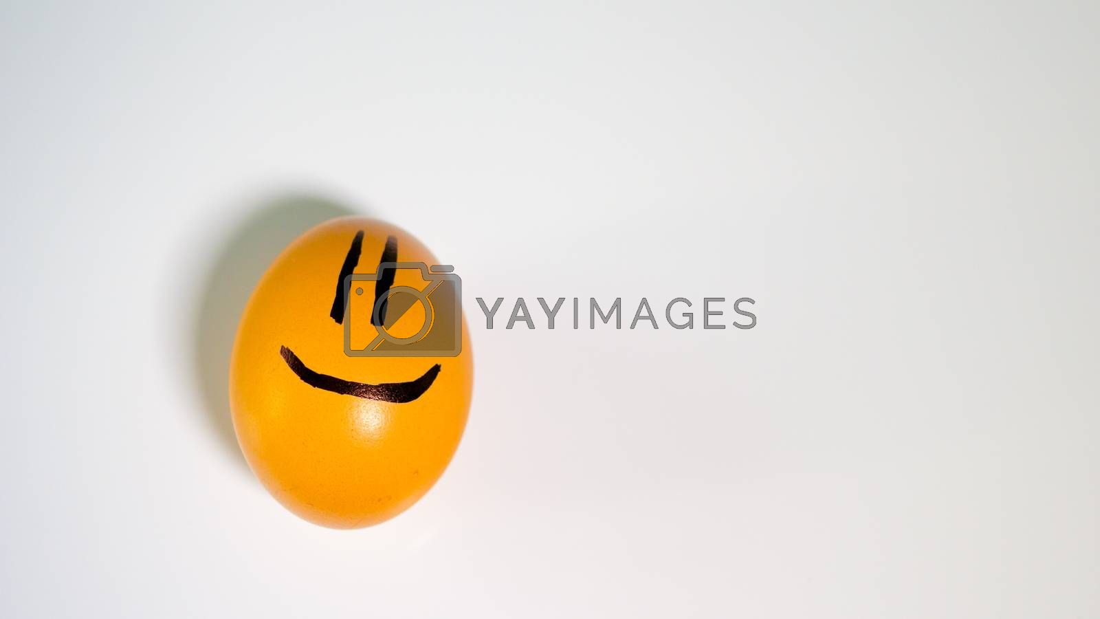 yellow chicken egg with a smiley on a white background